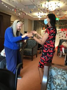 A picture containing senior woman dancing and a ceiling decorated with peace cranes. Activity for person with dementia. Senior woman with long hair.