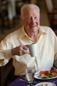 A senior man holding eating a gourmet breakfast, holding a cup of tea. Elderly man in retirement home Canada.