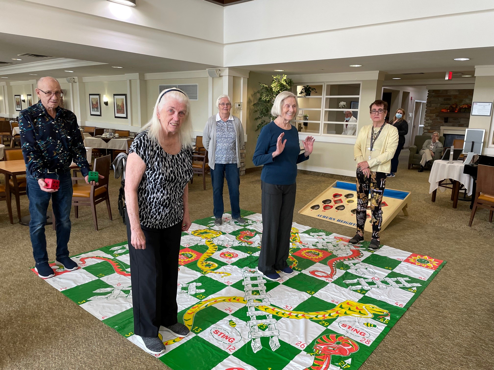 Group of people with grey hair playing a giant game of snakes and ladders