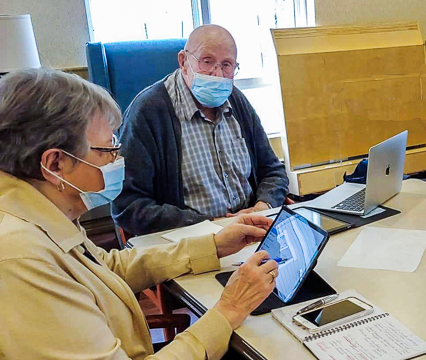 Senior man using a laptop and senior woman using an iPad and mobile phone.